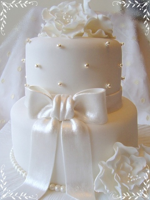 a pure white wedding cake decorated with edible beads, a large bow and sugar blooms on top is a very refined piece