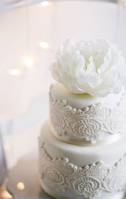 a gorgeous white wedding cake decorated with white lace and a large white sugar bloom is a very sophisticated piece