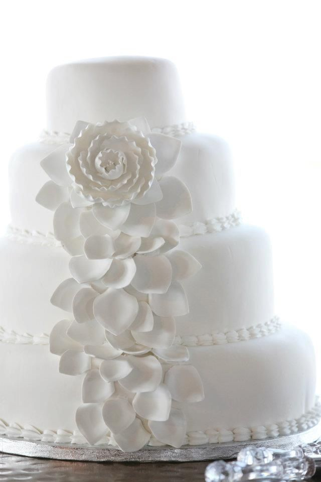 a chic white wedding cake decorated with edible beads and sugar blooms is a stylish and romantic piece to rock