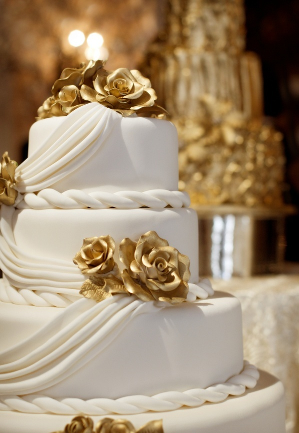 a white draped wedding cake with gold sugar roses is a fantastic idea for a modern glam wedding