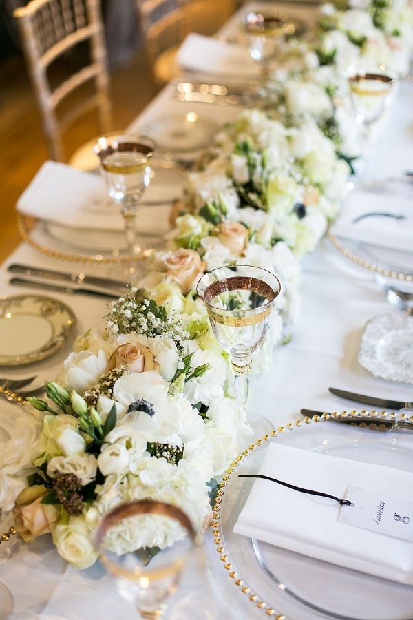 an exquisite gold and white wedding tablescape with a white bloom table runner, gold rimmed glasses and chargers and gold cutlery