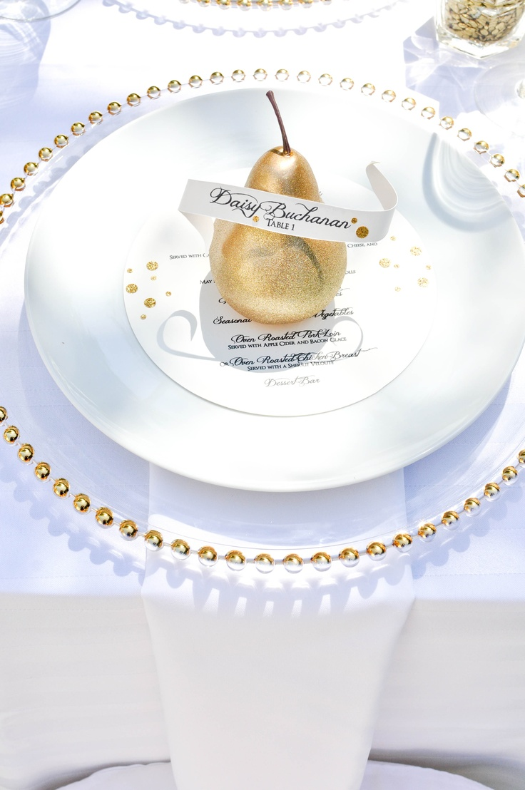 a pretty and refined wedding place setting with a gold edge charger, white plates and a gilded pear plus a card