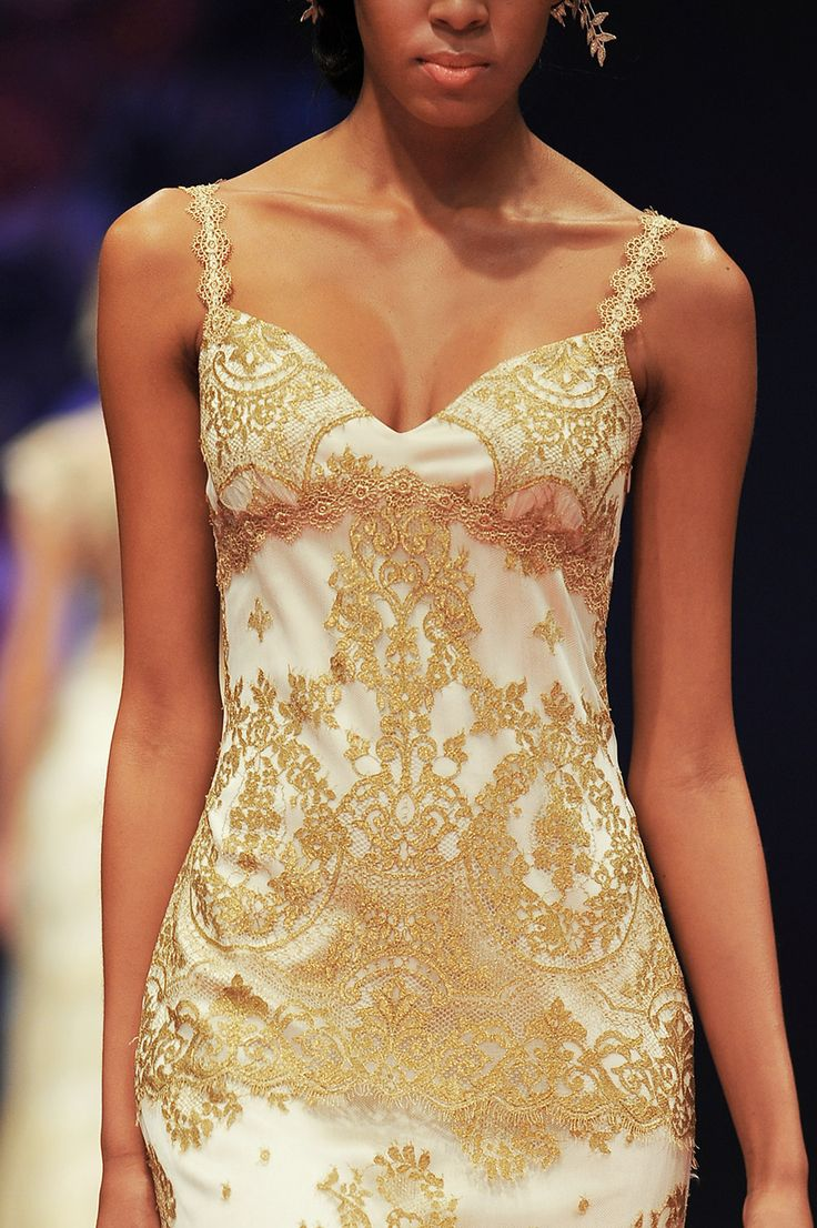 a sheath white wedding dress with gold lace appliques and gold straps looks very statement like