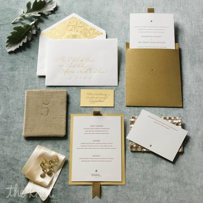 a stylish white and gold wedding invitation suite with pretty printing and ribbons for a refined wedding