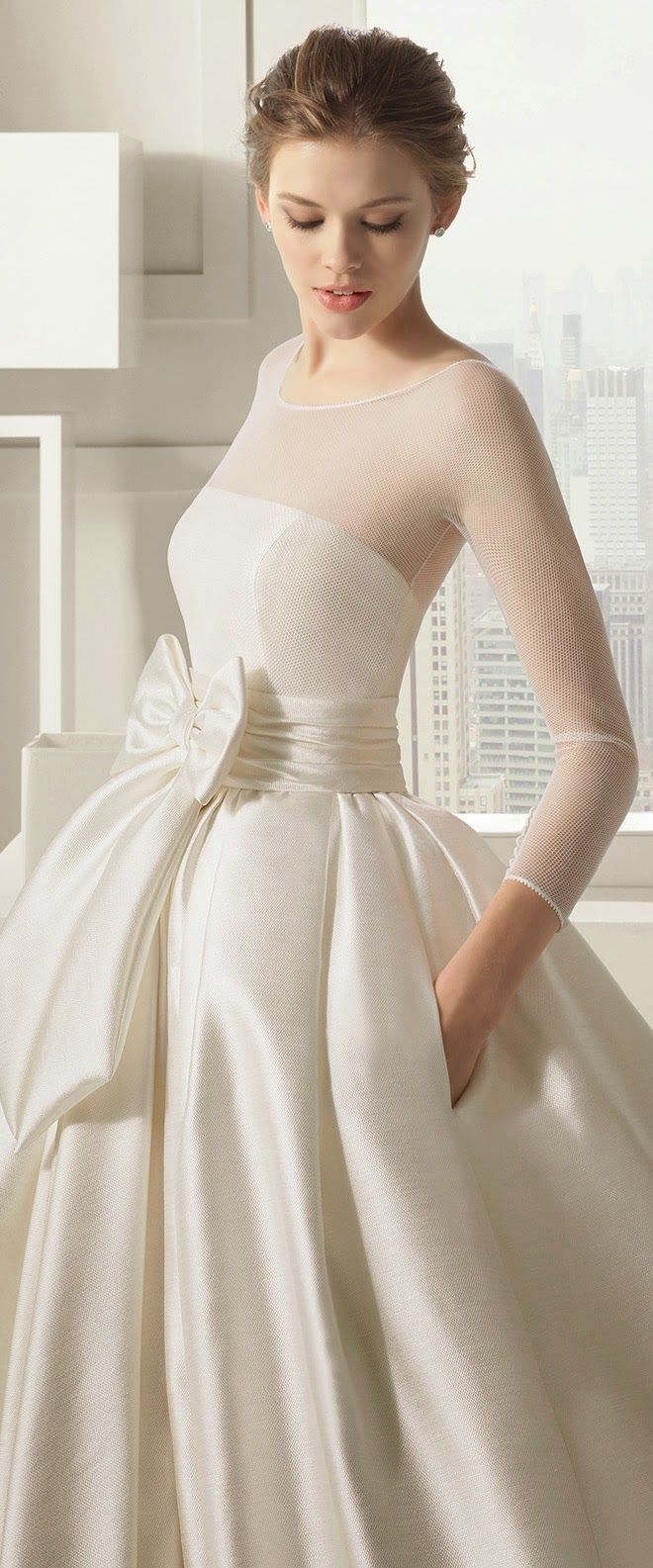 a romantic modern wedding ballgown with an illusion neckline, a large bow, long sleeves and a pleated skirt is wow