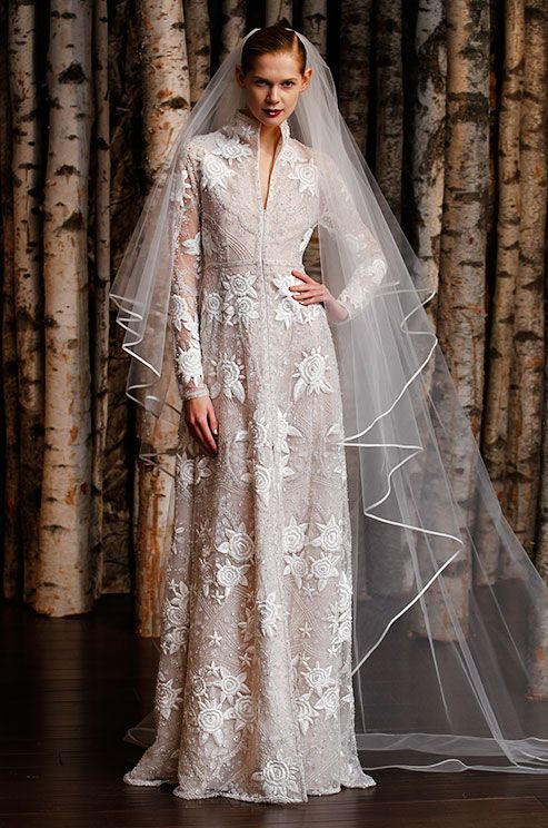 a whimsy wedding dress of textural fabric, with star and sun appliques and embroidery plus a long veil for a statement look