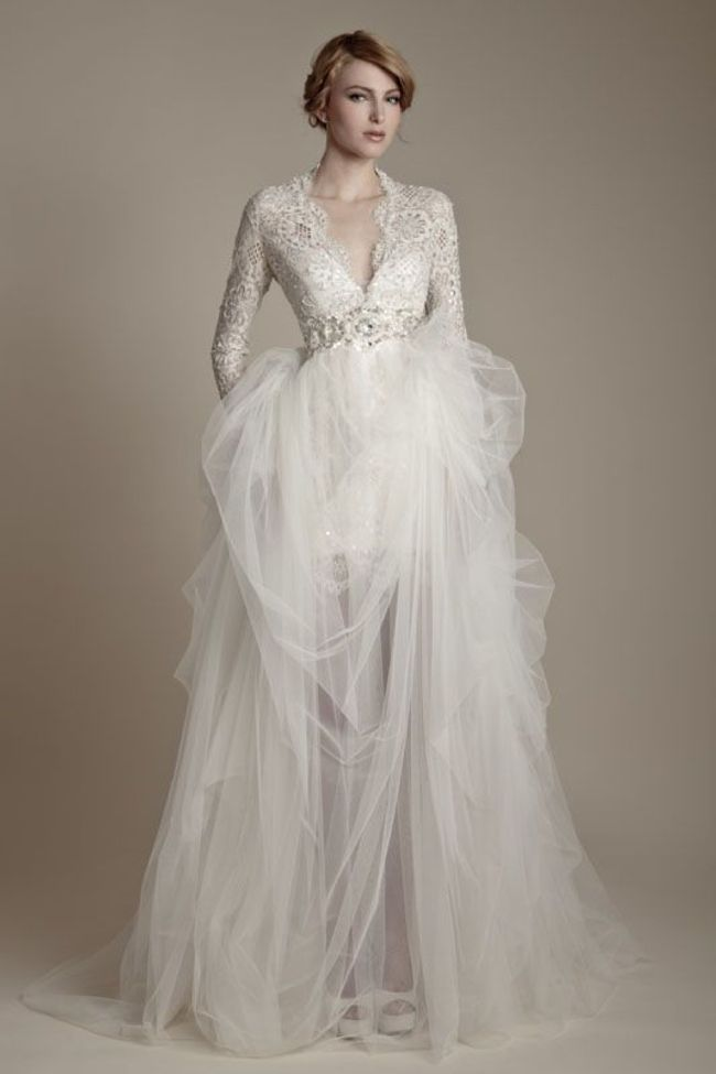 a chic winter wedding dress with a lace bodice with a V neckline, long sleeves, an embellished sash and a layered skirt