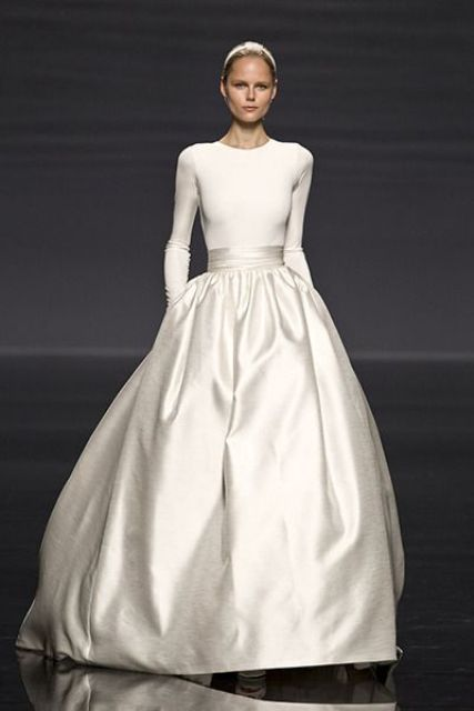 a modern wedding ballgown with a matte white bodice with long sleeves and a high neckline, with a shiny full skirt