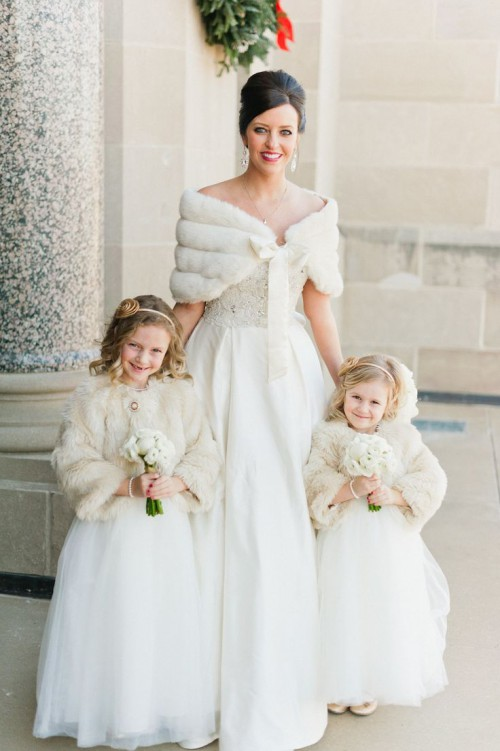 a romantic vintage-inspired wedding ballgown with a lace bodice and a plain full skirt plus a faux fur coverup