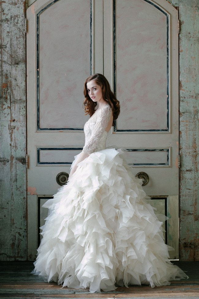 a whimsy wedding ballgown with a lace bodice with long sleeves, a cutout back and a layered feathered skirt looks very cool