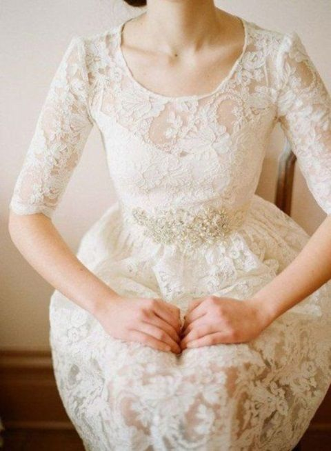 a vintage inspired lace A line wedding dress with a high neckline and short sleeves plus an embellished sash