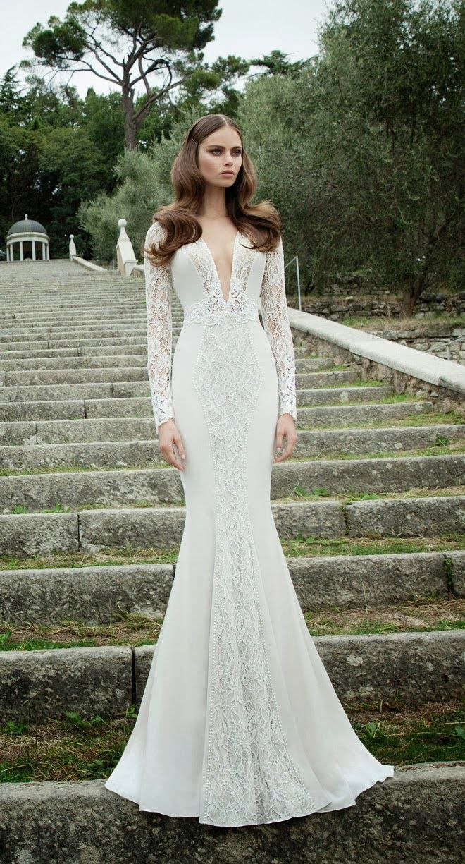 a gorgeous mermaid wedding dress of lace, with a plunging neckline, long sleeves and a creative skirt of plain fabric and lace