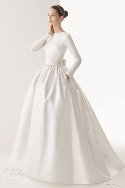 a plain wedding ballgown with a bodice with long sleeves, a high neckline and a pleated skirt with pockets looks non-typical and chic