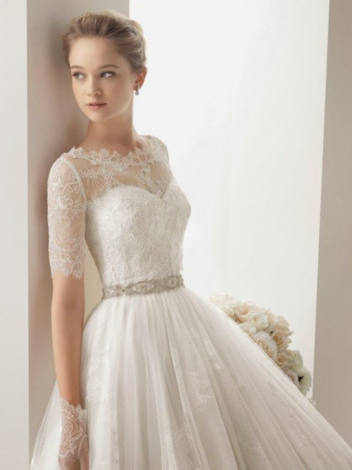 a romantic vintage-inspired wedding ballgown of lace, with a high neckline and short sleeves, an embellished sash and lace gloves to finish off the look