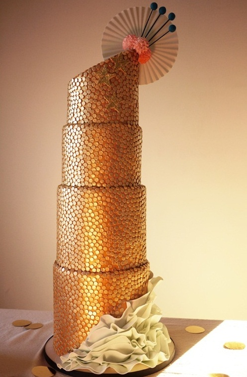 an outstanding gold penny wedding cake with sugar ruffles at the bottom and some Japan inspired sugar decor