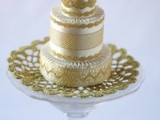 an exquisite gold and white patterned wedding cake with lace and some fringe on top is a stylish option