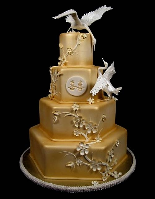a unique octagonal gold wedding cake with sugar blooms and swans looks very spectacular