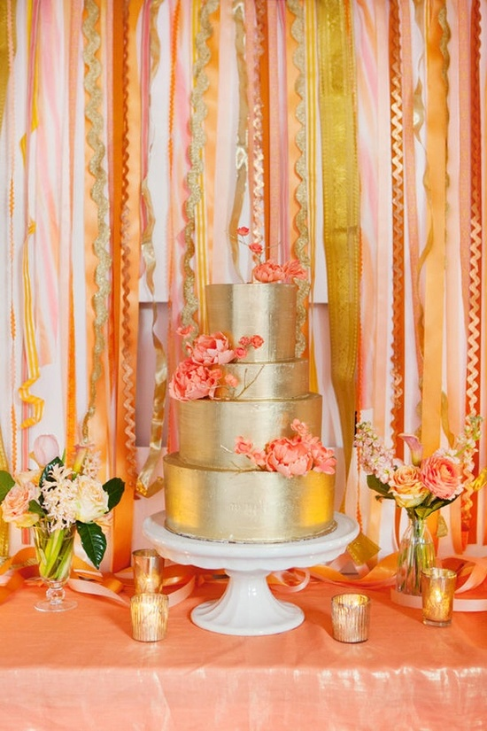 a shiny glam gold wedding cake with coral sugar blooms is a nice idea for a modern bright wedding