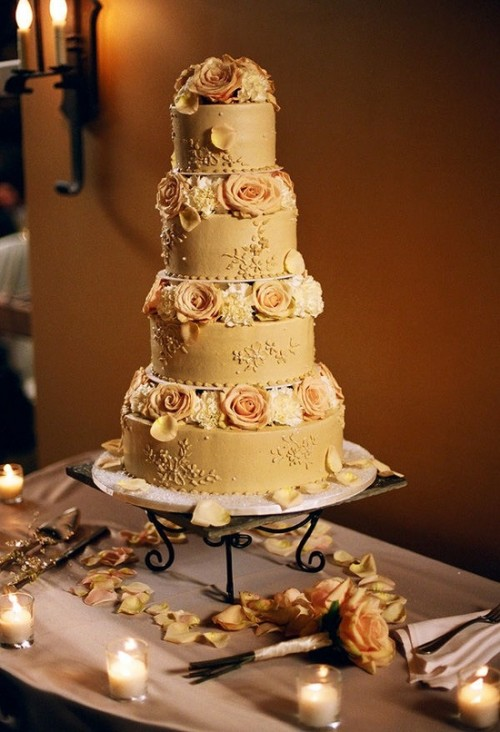 a beautiful gold wedding cake with various patterns and peachy and white blooms is a chic and cool idea
