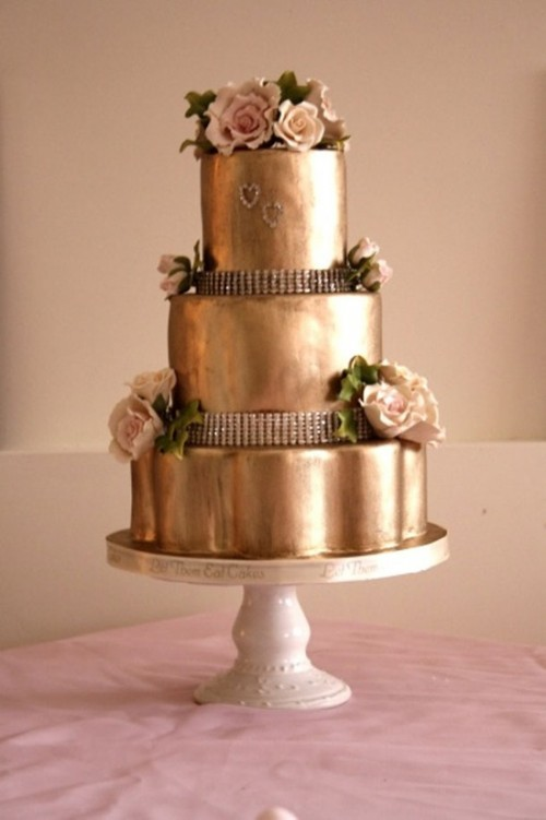 a shiny gold wedding cake with embellishments, blush blooms and leaves looks super refined and chic