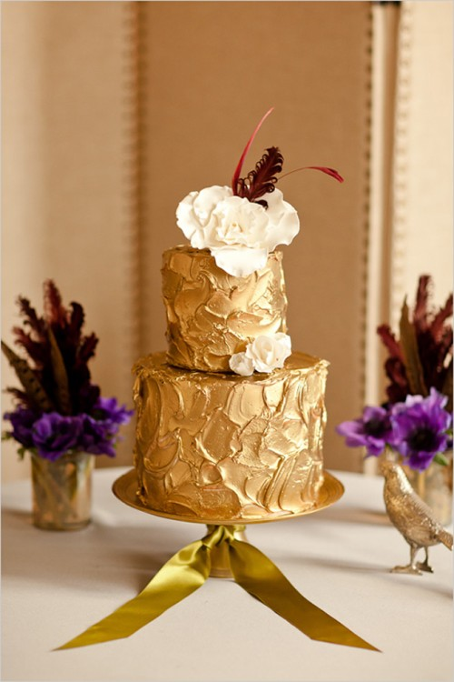 a gold textural wedding cake with sugar blooms and feathers on top for a chic and non-typical wedding dessert table