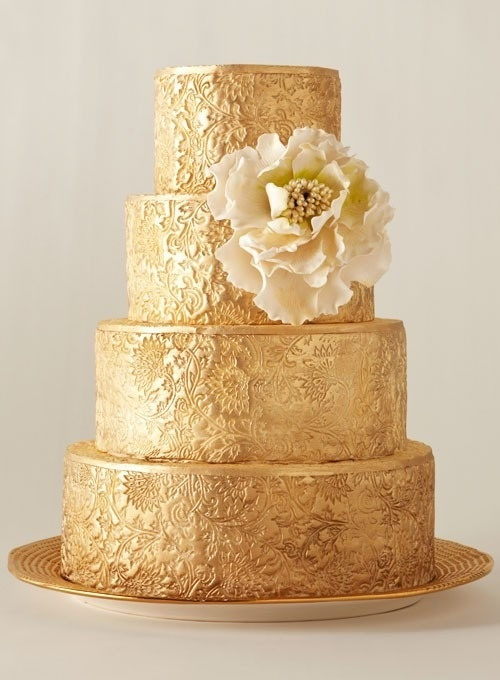 a gold patterned wedding cake with a neutral sugar bloom is a great idea for a very exquisite wedding
