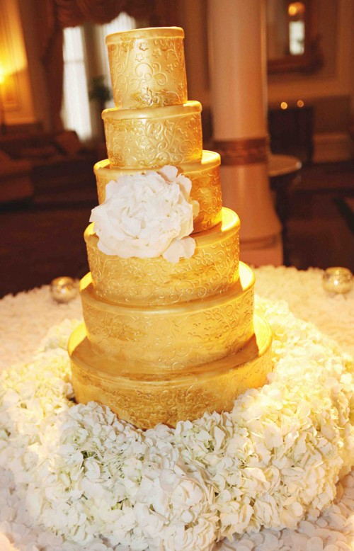 a multi-tier gold wedding cake with patterns and with a large sugar bloom for a very refined wedding