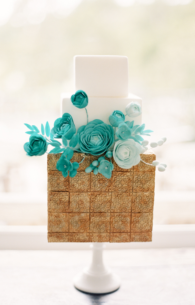 a very catchy wedding cake in white and covered with gold cookies, with aqua and turquoise sugar blooms is fantastic