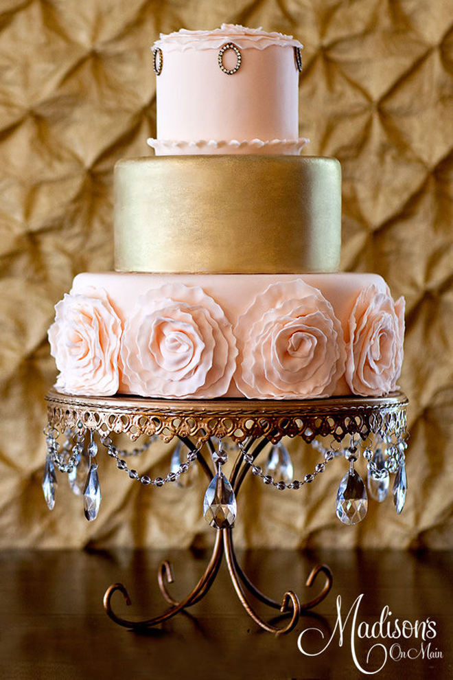 a sophisticated wedding cake with blush pink and gold tiers, with sugar blooms and embellishments for a refined wedding