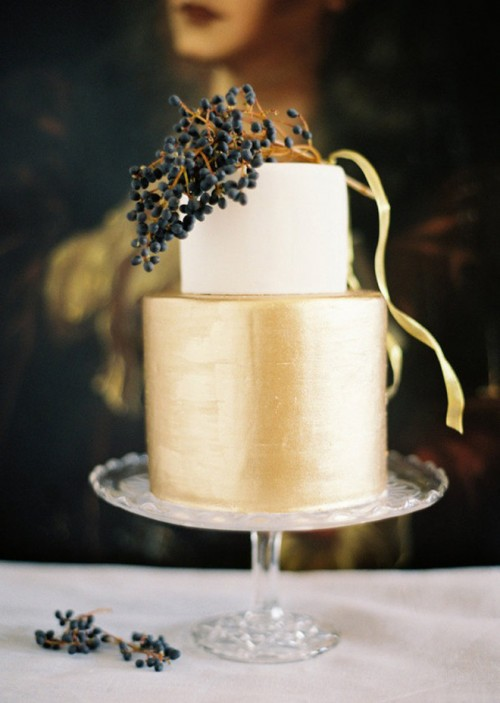 a modern stylish wedidng cake in white and gold, topped with privet berries and ribbons is very stylish and chic