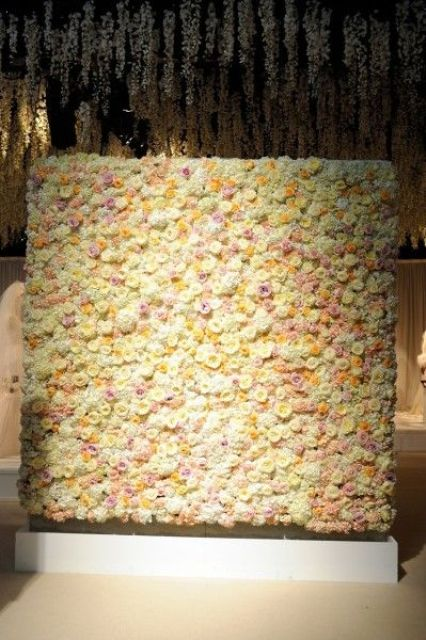 a beautiful floral wall with ivory, yellow and pink roses accented with additional lights