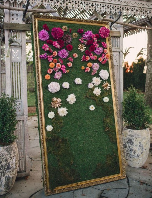 a refined framed wall with moss and chaotically attached blooms in white, orange and bright pink