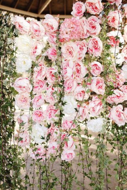 a lush pink peony and greenery floral wall as a beautiful and romantic wedding backdrop