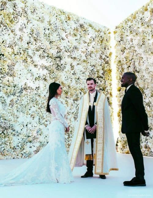 two white floral walls with built-in lights in between to accent the backdrop and the couple