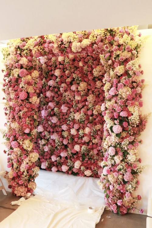 a lush red, white and pink floral wall backdrop and a matching arch to dive into the florals completely