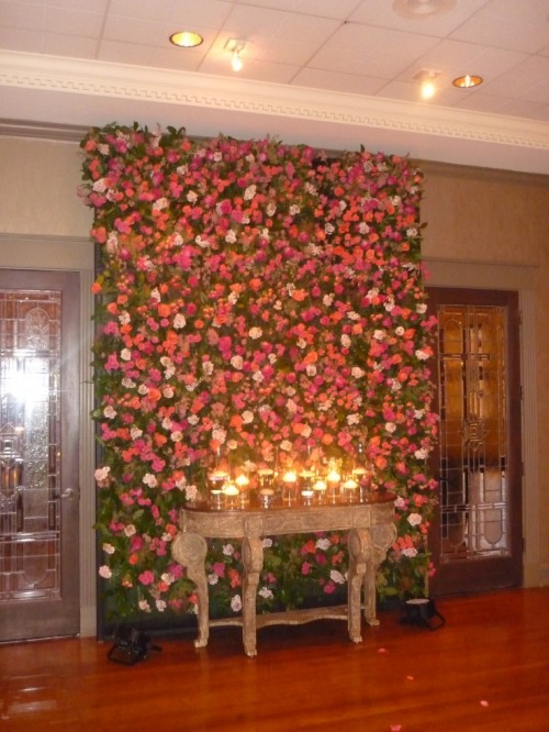 a lush floral wall with blush, orange and pink blooms can double as a wedding ceremony backdrop and as a lounge backdrop, too