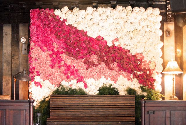 a bright floral wall in white, fuchsia and light pink blooms designed with a color block effect