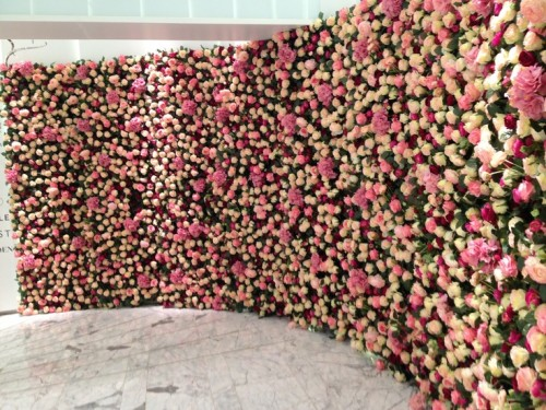 a long curved floral wall with white and pink roses is a gorgeous wedding and photo booth backdrop