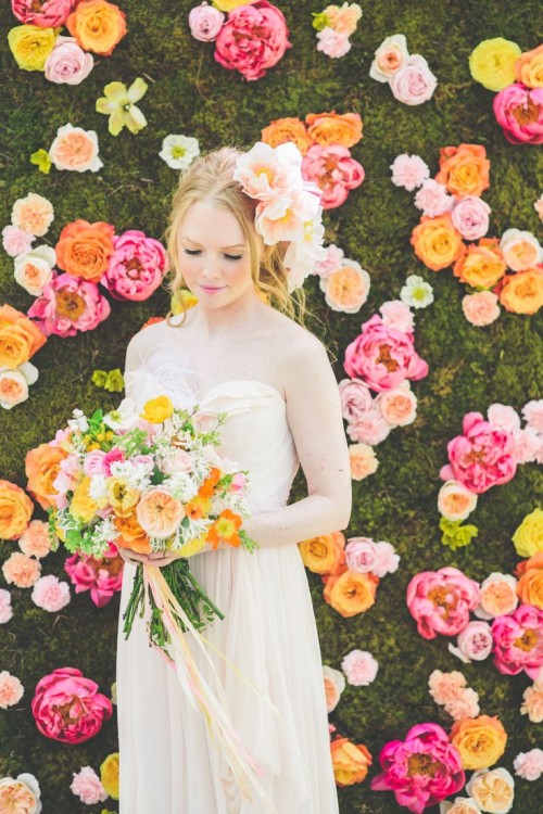 a bright floral wall with orange, pink, peachy and blush blooms and a moss background