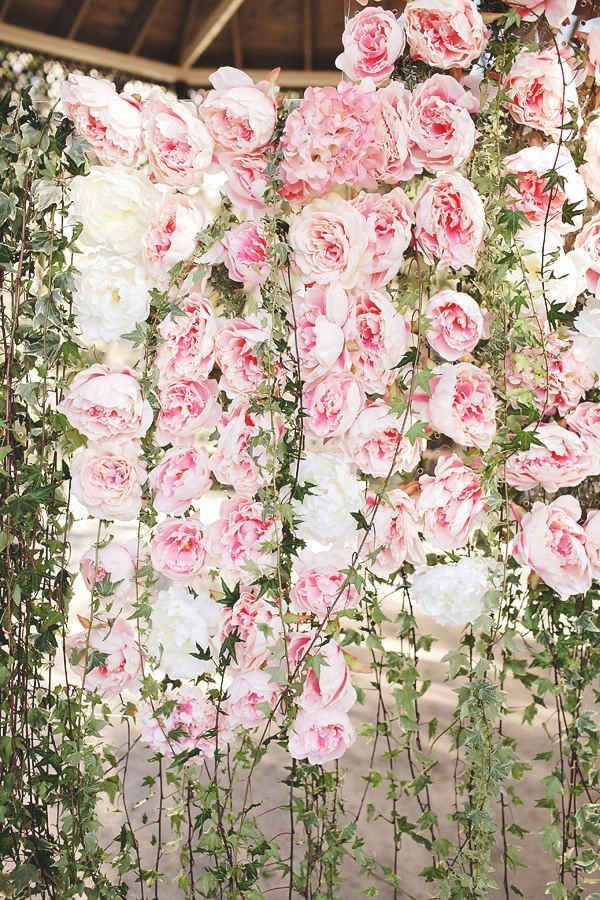 a pink peony wall with greenery is a very cute and romantic wedding decor idea