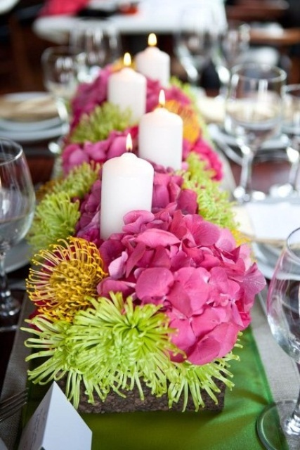a colorful spring wedding centerpiece in pink, yellow and green plus pillar candles in a box