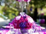 a purple and hot pink floral centerpiece is a bold and statement idea for a spring wedding