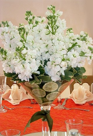 a white floral centerpiece with lemon slices in a cone-shaped vase is a fresh and bright idea for a spring wedding