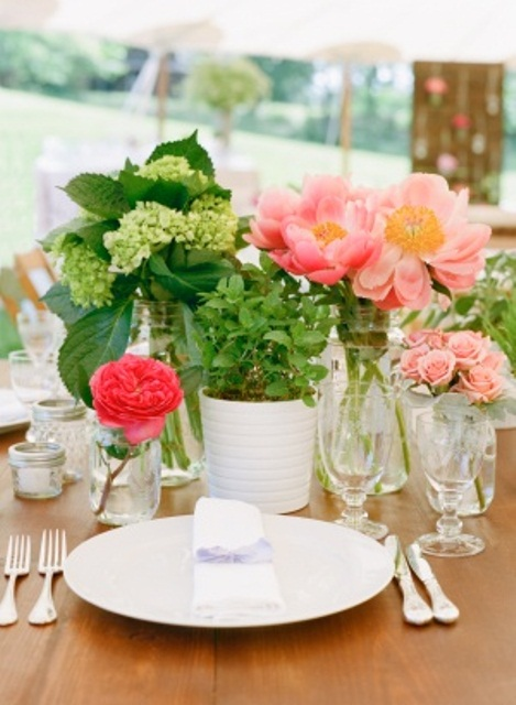 a bright pink and red floral centerpiece paired with a green hydrangea one for a bold spring wedding