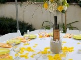 a bright spring wedding centerpiece composed of white and yellow blooms and some blooming branches