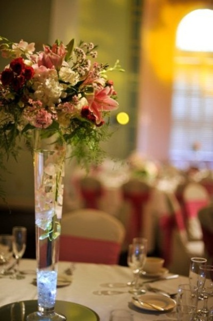 a tall pink and white floral centerpiece with greenery in a tall clear vase for a spring wedding