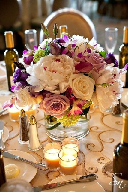 a lush floral centerpiece of blush, pink, purple and green blooms for a spring wedding