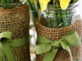 jars with yellow daffodils, burlap and green bows are cute and cool rustic wedding centerpieces