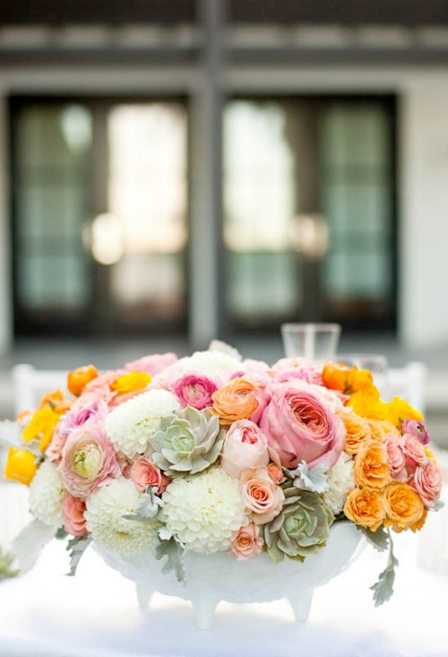 a white pot on legs with orange, pink and blush blooms and pale succulents is a chic and lush idea