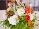 a bright spring wedding centerpiece of red and white blooms, greenery and branches for more texture